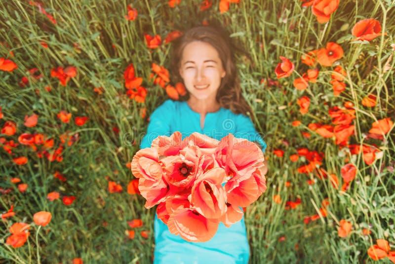 Mujer joven feliz que miente en prado de la flor fotos de archivo