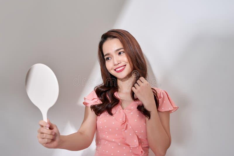 Mujer joven feliz que mira en el espejo imagenes de archivo