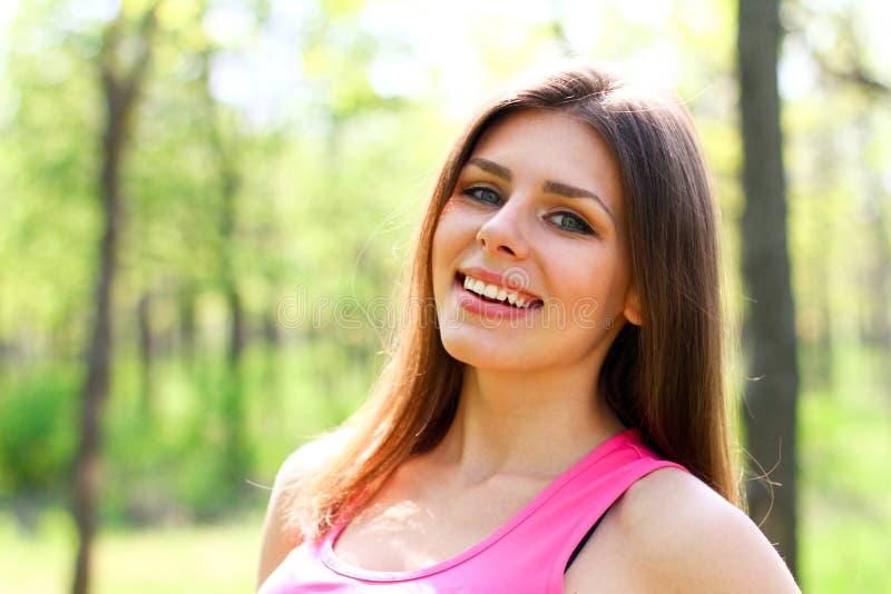 Mujer joven feliz que mira la cámara en un parque del verano imagen de archivo