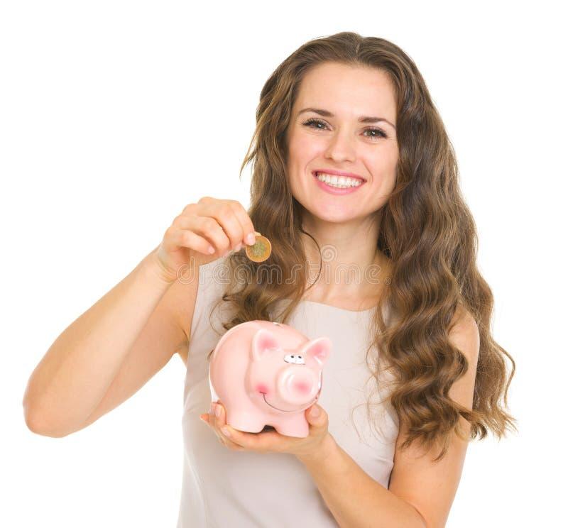 Mujer joven feliz que pone la moneda en la hucha imagenes de archivo