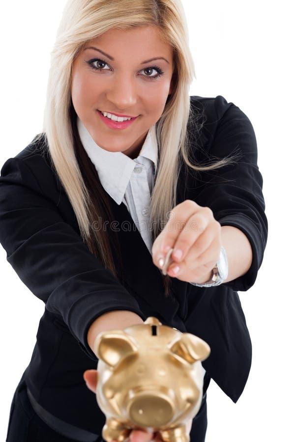 Mujer joven feliz que pone la moneda en la hucha fotografía de archivo