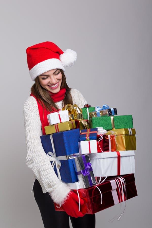 Mujer joven feliz que ríe llevando muchos presentes fotografía de archivo