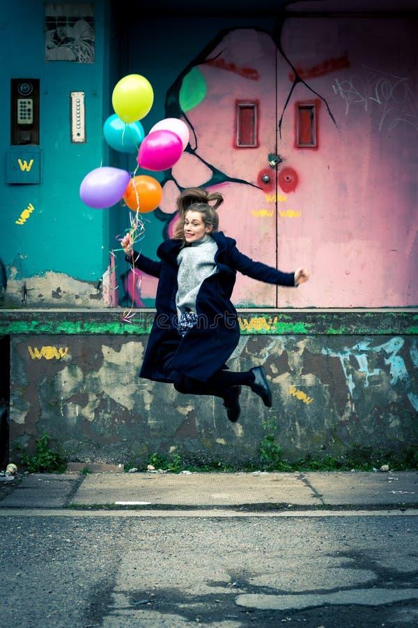 Mujer joven feliz que salta arriba mientras que el sostenerse hincha imagenes de archivo
