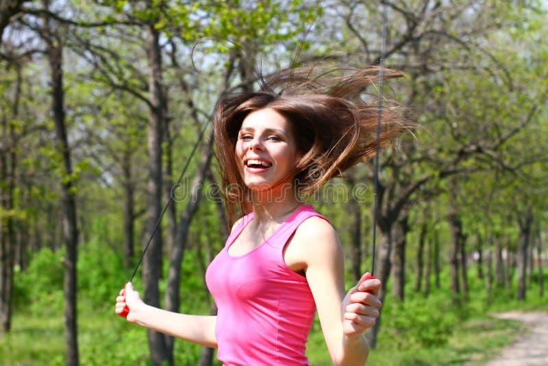 Mujer joven feliz que salta con una cuerda que salta en un parque del verano foto de archivo