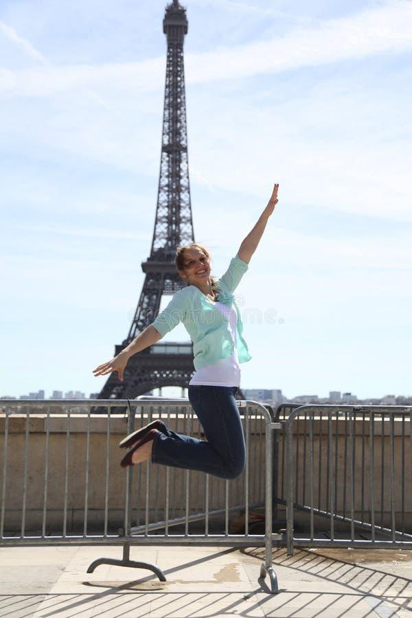 Mujer joven feliz que salta contra torre Eiffel fotografía de archivo libre de regalías