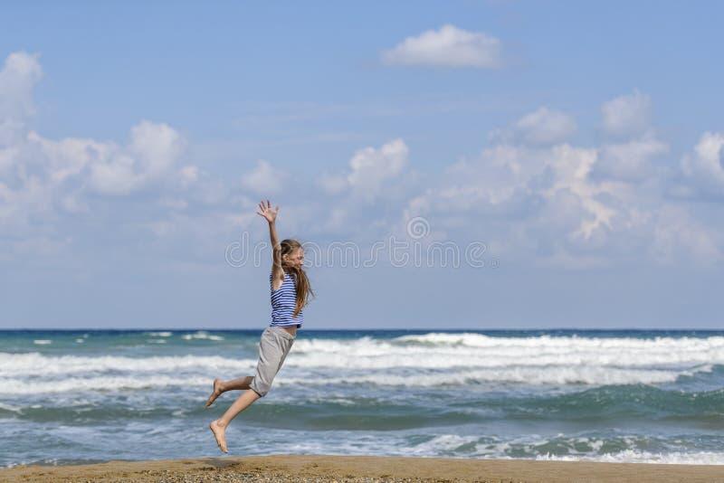 Mujer joven feliz que salta en la playa imagenes de archivo