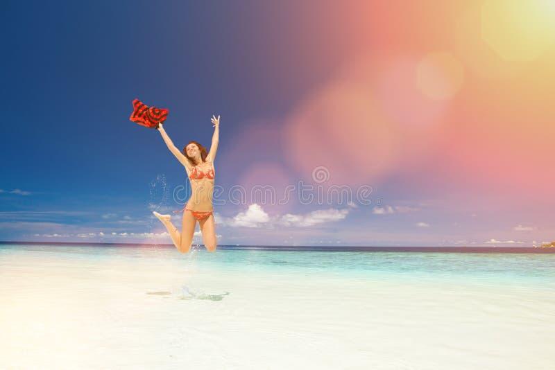 Mujer joven feliz que salta en la playa Forma de vida feliz Arena blanca, cielo azul y mar del cristal de la playa tropical Vacac imagen de archivo