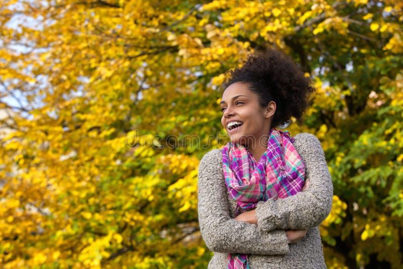 Mujer joven feliz que se coloca al aire libre en caída imagenes de archivo