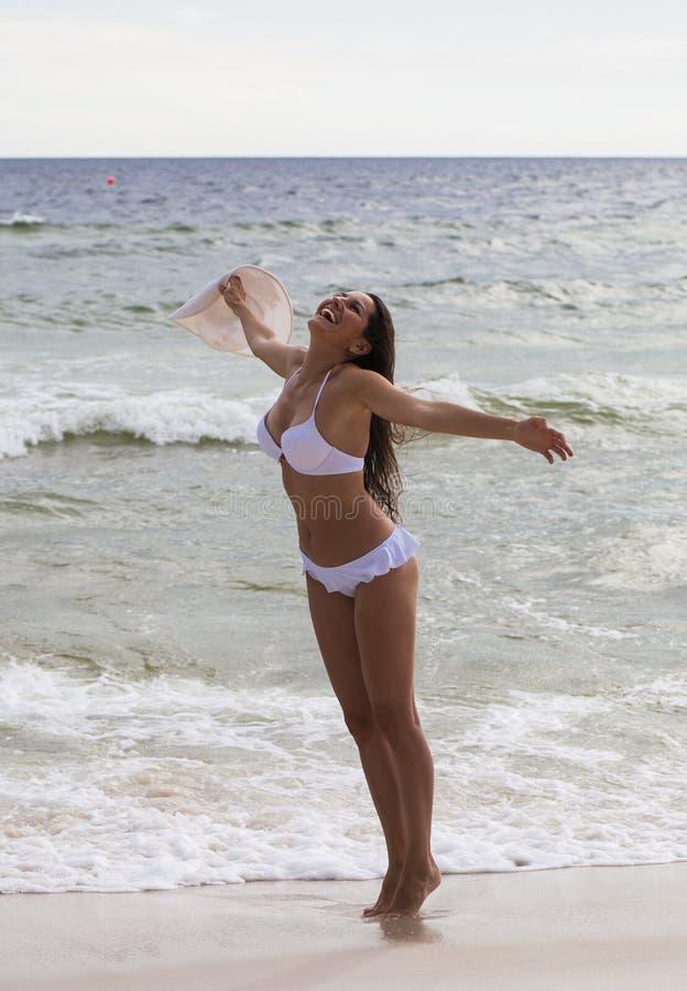 Mujer joven feliz que se coloca en la playa y la risa imagen de archivo