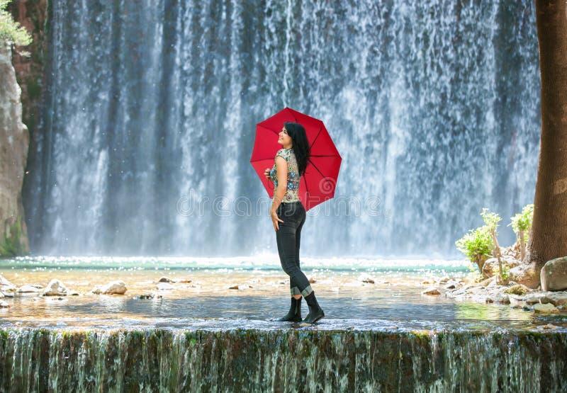 Mujer joven feliz que se coloca en una cala con un paraguas rojo delante de una caída impresionante del agua imagenes de archivo