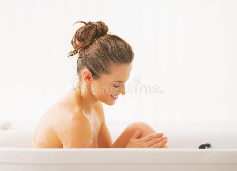 Mujer joven feliz que se lava en bañera foto de archivo