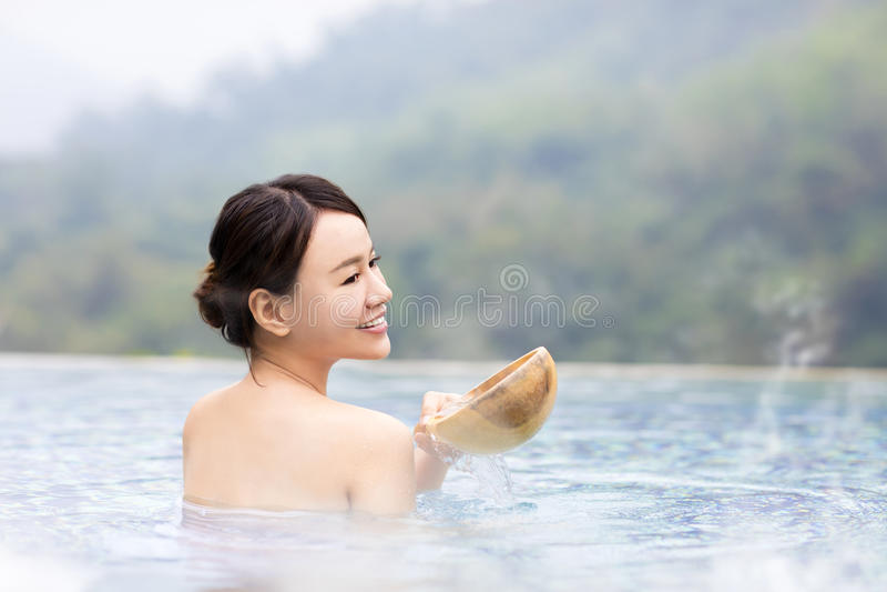 Mujer joven feliz que se relaja en aguas termales imágenes de archivo libres de regalías