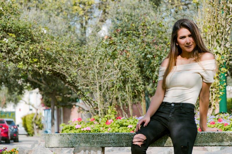 Mujer joven feliz que se sienta en banco en modelo de moda elegante del parque de la ciudad fotografía de archivo