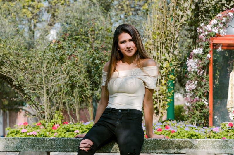 Mujer joven feliz que se sienta en banco en modelo de moda elegante del parque de la ciudad fotos de archivo libres de regalías