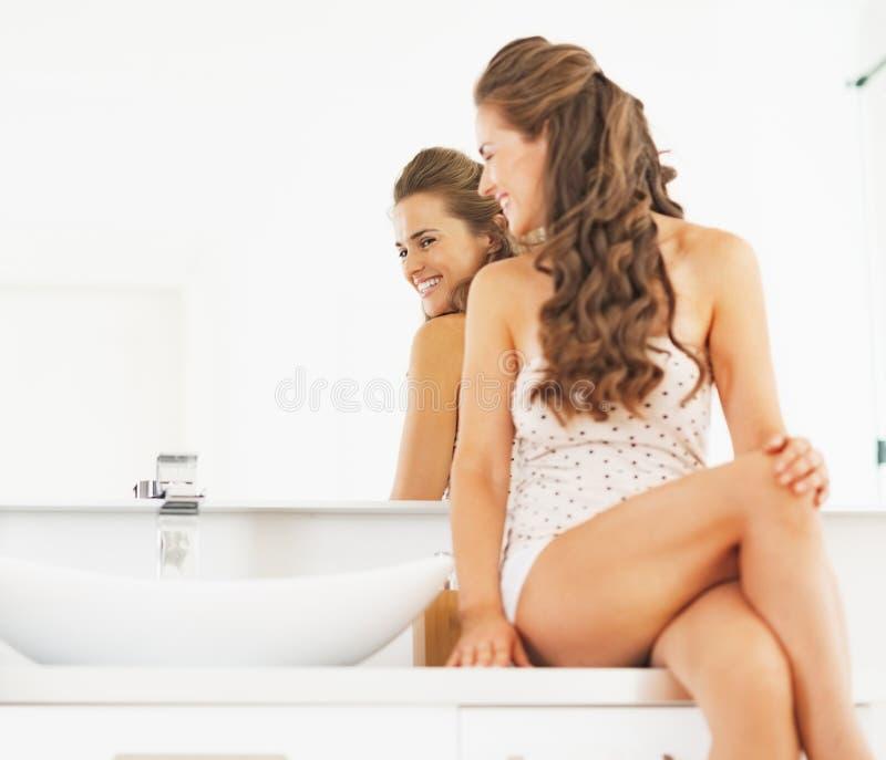 Mujer joven feliz que se sienta en cuarto de baño y que mira en espejo imagenes de archivo