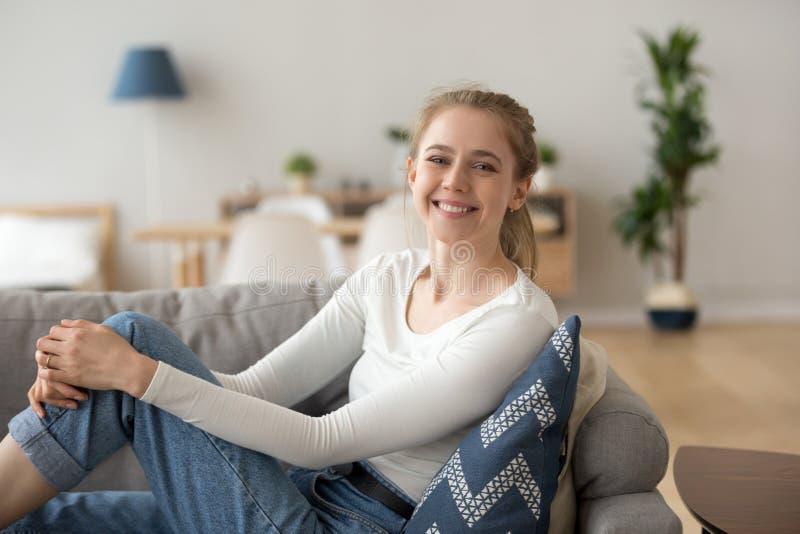 Mujer joven feliz que se sienta en el sofá en casa foto de archivo