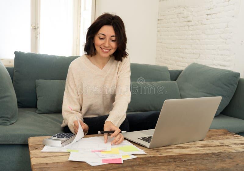 Mujer joven feliz que se sienta en el sof? rodeado por los papeles que calculan costos y cuentas que pagan imagenes de archivo
