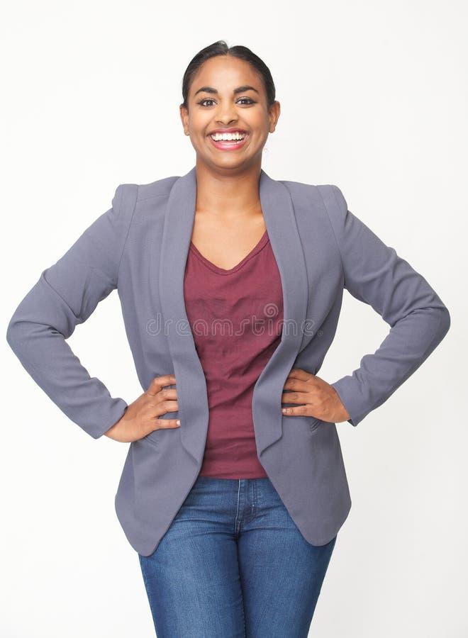Mujer joven feliz que sonríe con las manos en cadera fotos de archivo