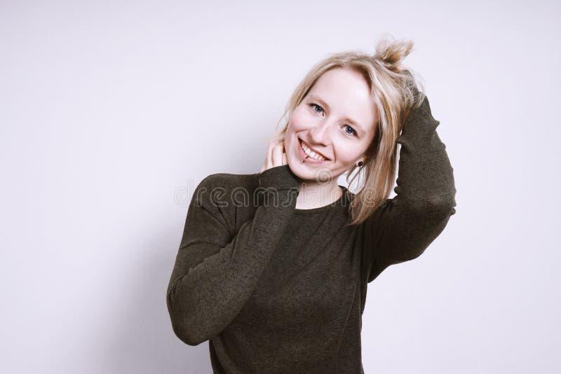 Mujer joven feliz que sonríe con las manos en pelo fotografía de archivo libre de regalías