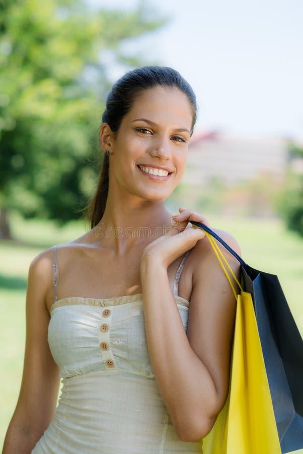 Mujer joven feliz que sonríe con los bolsos de compras imágenes de archivo libres de regalías
