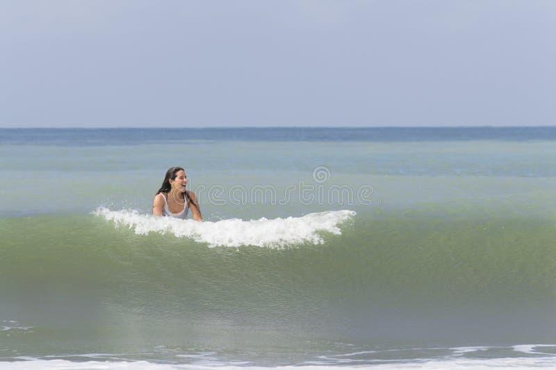 Mujer joven feliz que sonríe en el océano imagen de archivo