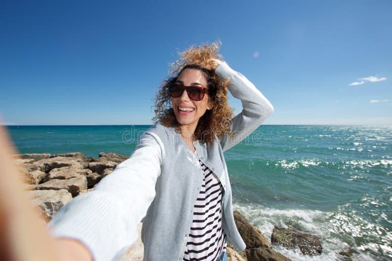 Mujer joven feliz que sonríe y que toma el selfie por el mar imagen de archivo