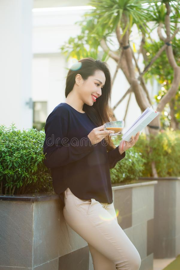 Mujer joven feliz que sostiene el libro encariñado con la literatura que analiza la novela durante el tiempo libre en la terraza  imagenes de archivo
