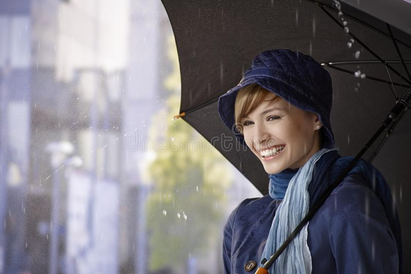 Mujer joven feliz que sostiene el paraguas en lluvia foto de archivo libre de regalías