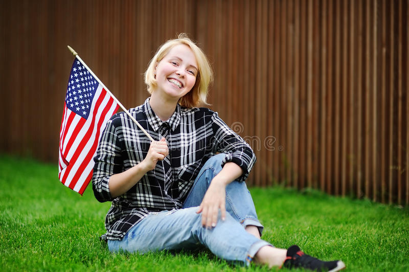 Mujer joven feliz que sostiene la bandera americana imagen de archivo libre de regalías