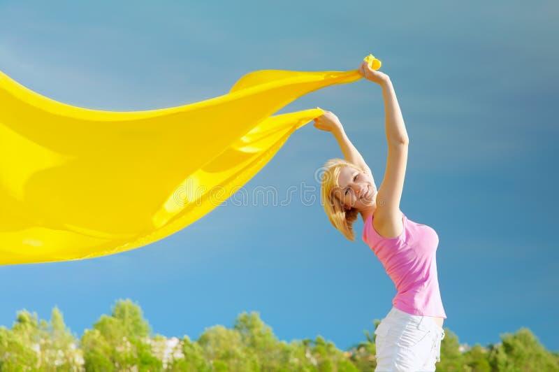 Mujer joven feliz que sostiene la bufanda amarilla en el viento fotos de archivo