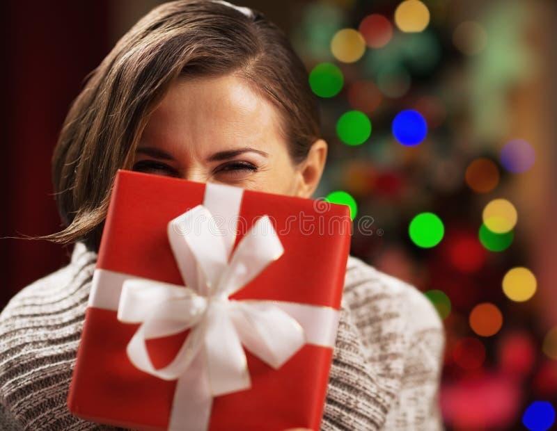 Mujer joven feliz que sostiene la caja del regalo de Navidad delante de la cara foto de archivo