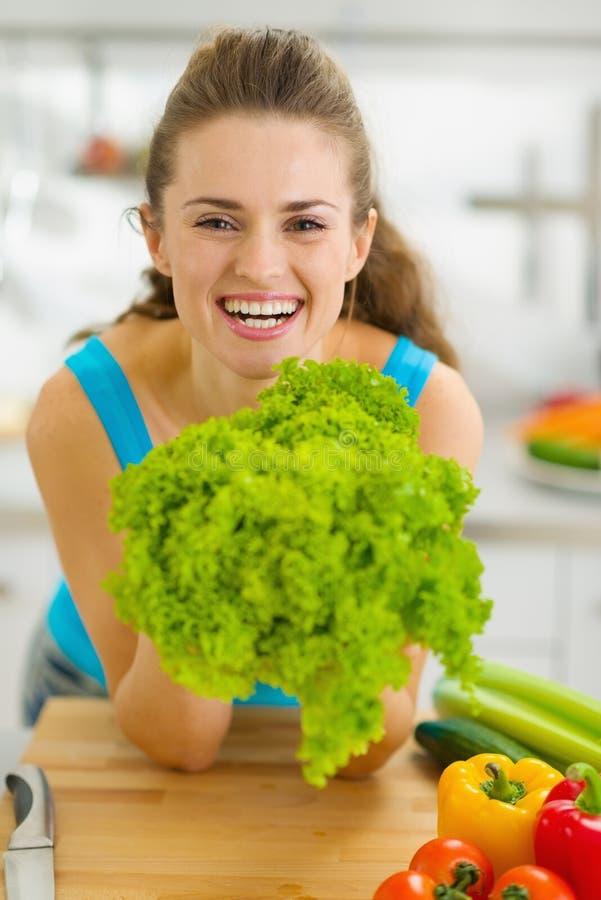 Mujer joven feliz que sostiene la ensalada verde en cocina foto de archivo