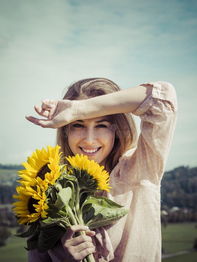 Mujer joven feliz que sostiene los girasoles imagenes de archivo