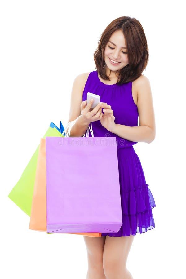 Mujer joven feliz que sostiene los panieres y el teléfono móvil imagenes de archivo