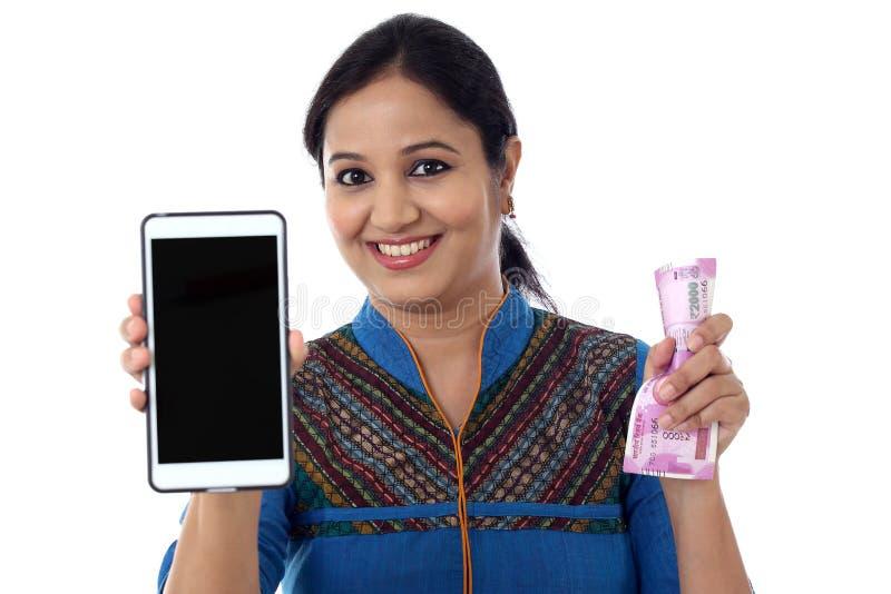 Mujer joven feliz que sostiene moneda india y el teléfono móvil foto de archivo