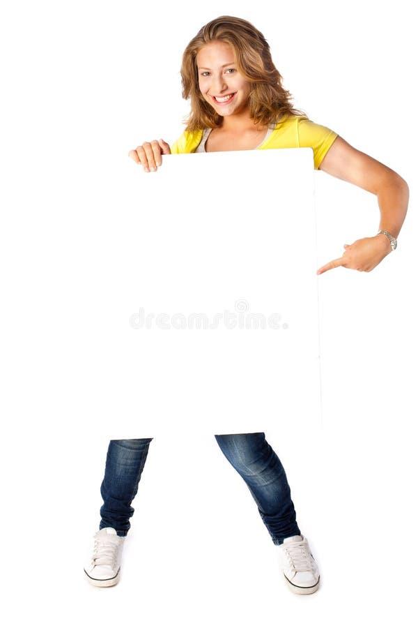 Mujer joven feliz que sostiene una cartelera en blanco foto de archivo