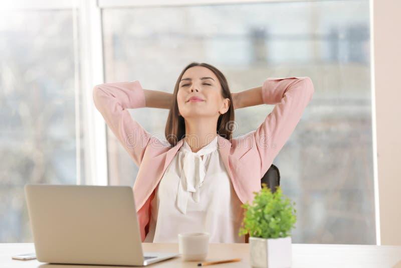 Mujer joven feliz que tiene resto corto en el lugar de trabajo imágenes de archivo libres de regalías