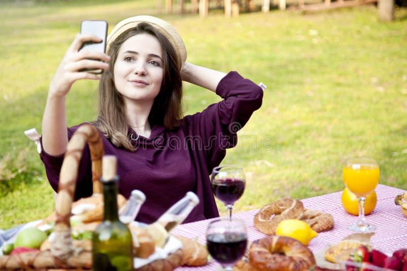 Mujer joven feliz que toma el retrato del selfie en la comida campestre fotos de archivo