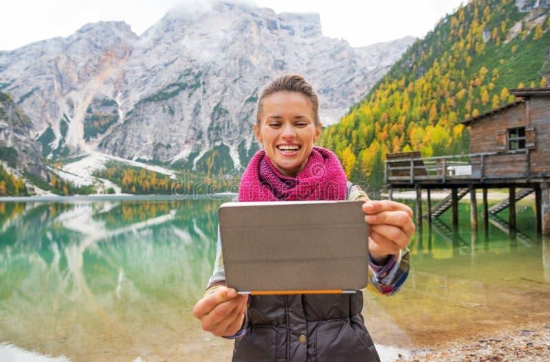 Mujer joven feliz que toma la foto con PC de la tableta en braies del lago imagen de archivo