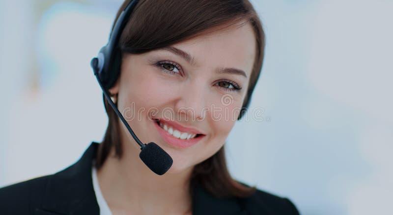 Mujer joven feliz que trabaja en el callcenter, usando las auriculares fotos de archivo