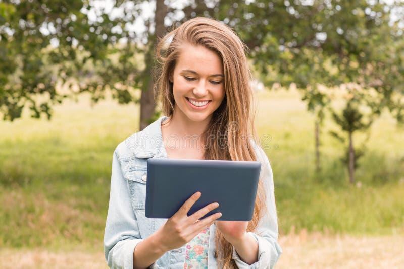 Mujer joven feliz que usa la PC de la tableta imagen de archivo