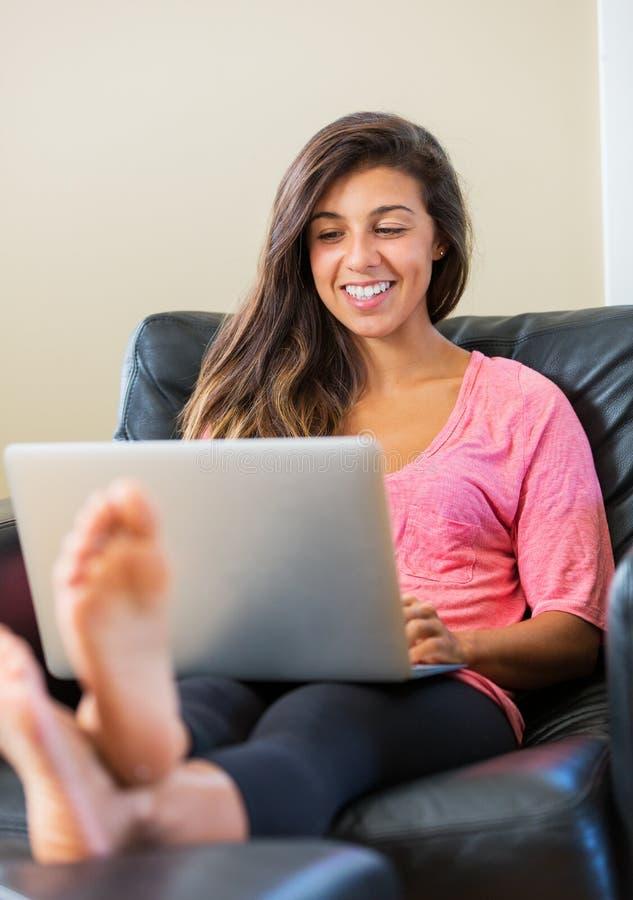 Mujer joven feliz que usa un ordenador portátil imagen de archivo