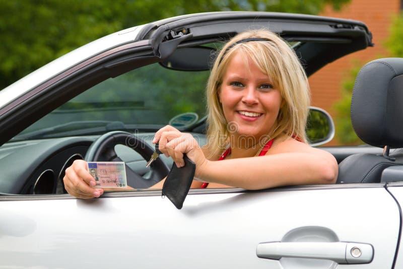 Mujer joven feliz sobre su nueva licencia de programas pilotos imagenes de archivo