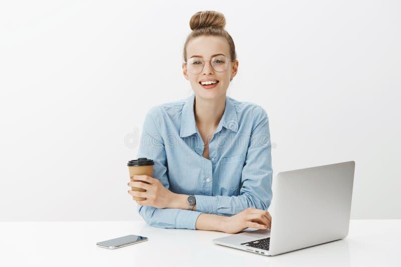 Mujer joven feliz trabajadora y despreocupada que trabaja en la oficina que lleva los vidrios transparentes y la camisa que se in fotos de archivo