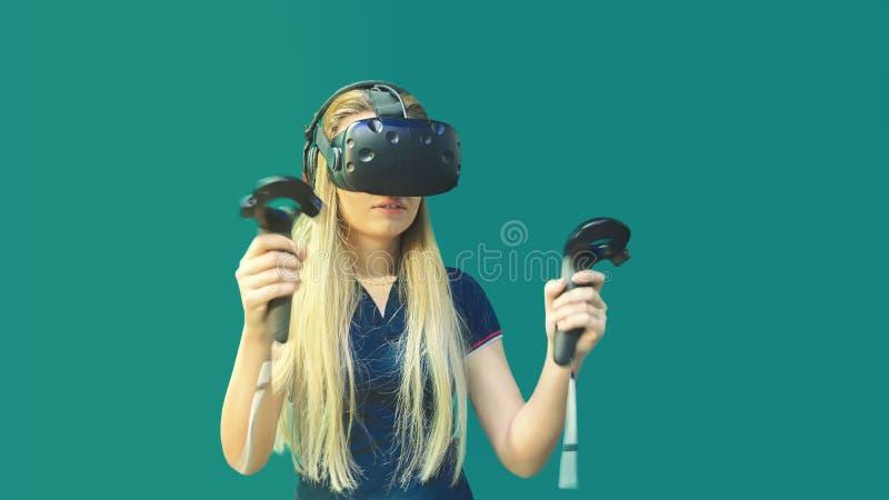 Mujer joven feliz usando la palanca de mando que juega a juegos sobre los vidrios de la realidad virtual interiores fotos de archivo libres de regalías