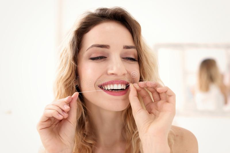 Mujer joven flossing sus dientes fotos de archivo
