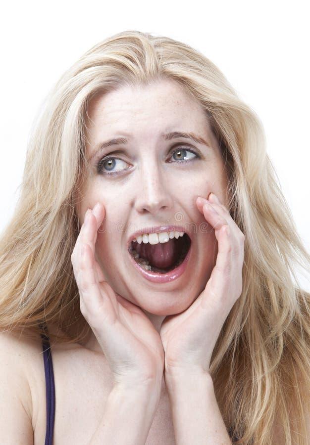 Mujer joven frustrada que grita contra el fondo blanco fotografía de archivo