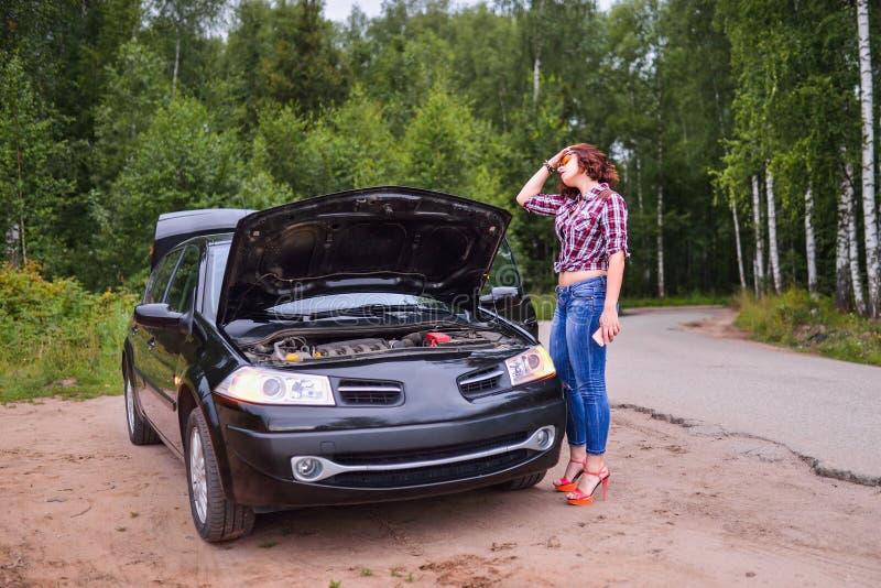 Mujer joven frustrada que mira el motor de coche analizado fotos de archivo