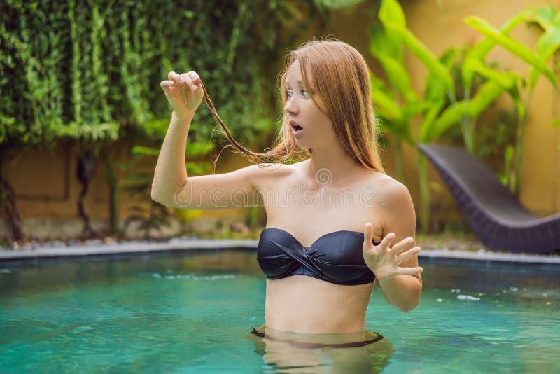 Mujer joven frustrada que tiene un mún pelo en la piscina r imagen de archivo