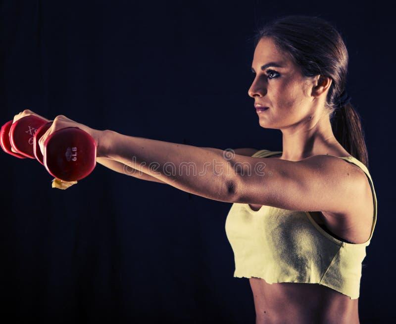 Mujer joven fuerte que hace aumentos del frente de la pesa de gimnasia imagenes de archivo